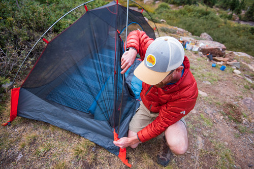 Man in red jacket setting up the Kelty Late Start 1 person tent in the woods