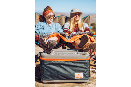 Two women sitting in camping chairs, using the Kelty Folding Cooler as a footstool