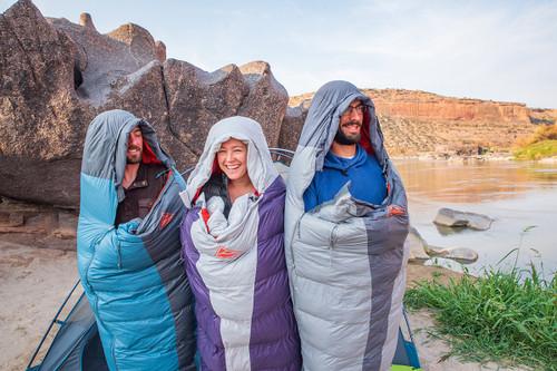 Group of 3 friends wearing Kelty Cosmic 20 sleeping bags, next to lake