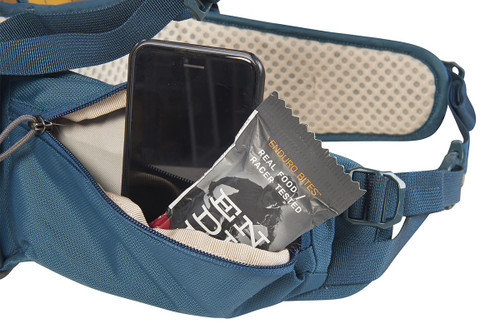 Close up of Kelty Zyp 38 backpack, showing snacks and phone stored in waist belt pocket