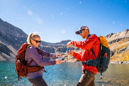 Couple wearing Kelty Zyp backpacks, opening cans of beer in front of an alpine lake
