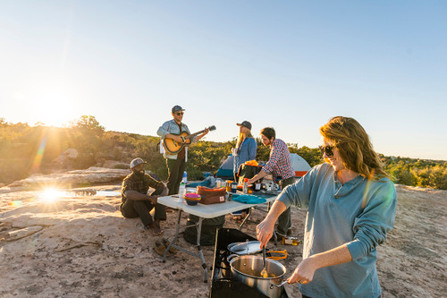 Group of campers making dinner and playing the guitar at sunset