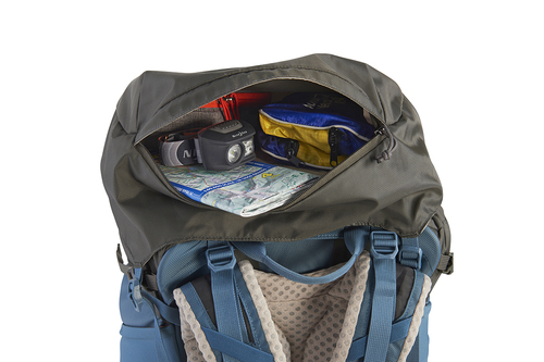 Close up of the top of Kelty Women's Zyro 64 backpack, with lid unzipped to show headlamp, medical kit, and map stored inside