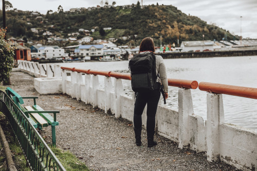Woman wearing Kelty Nomad travel pack, looking across the water at a harbor