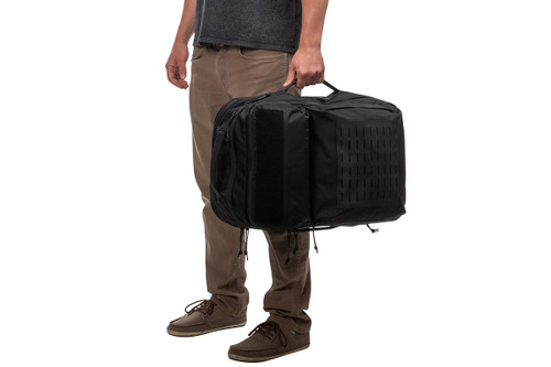 Man holding Kelty Nomad travel pack with side handle