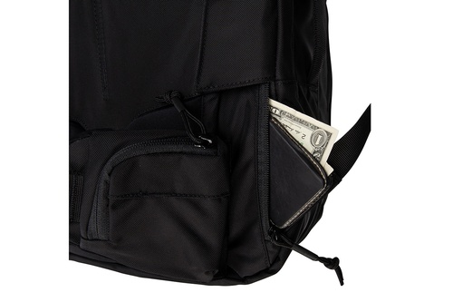 Close up of Kelty Nomad travel pack, showing small exterior zipper pocket with a wallet partially extending out of it