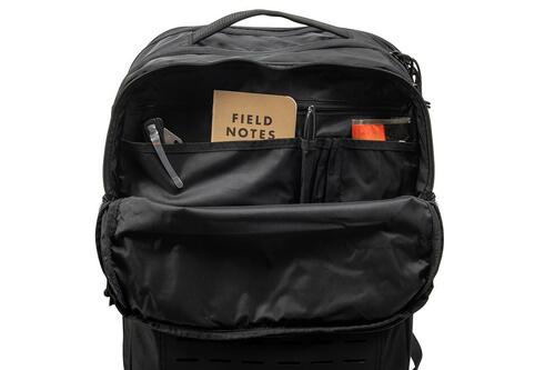 Close up of Kelty Nomad travel pack, partially unzipped to show multiple interior storage pockets with pens, a notebook, and other small items