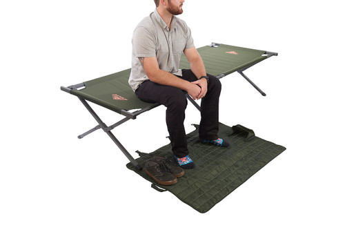 Man sitting on Kelty Discovery High Cot, using storage tote as a floor mat