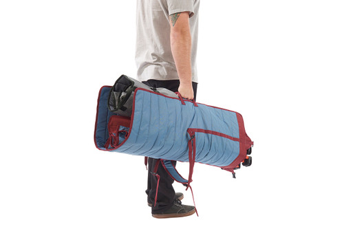 Man carrying Kelty Discovery Lowdown chair, blue/red, in its storage tote