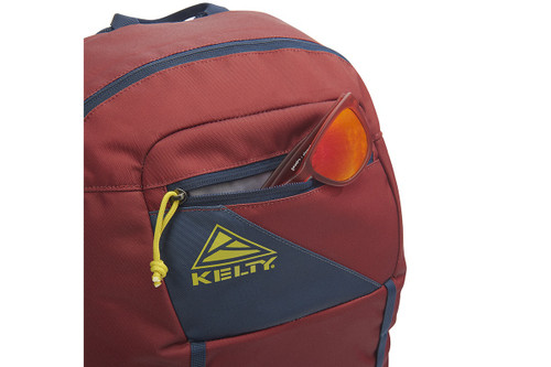Kelty Agate 24 Daypack, Red Ochre/Midnight Navy, with sunglasses partially extending from front pocket