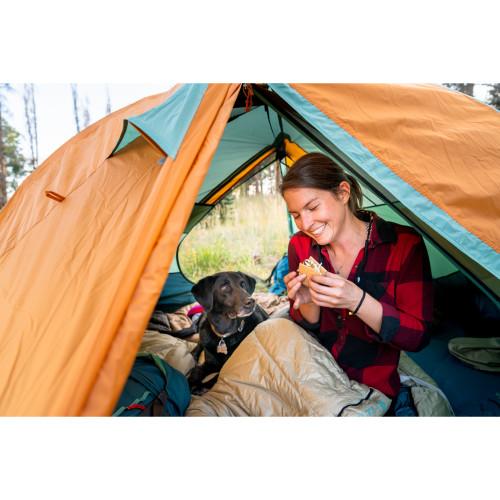 Woman eating s'more in her Kelty Tuck 20 sleeping bag