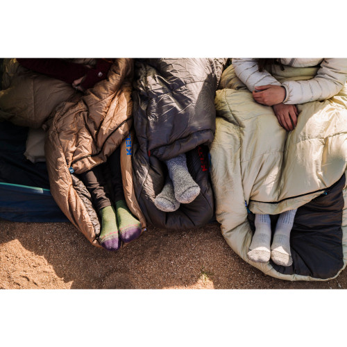 Close up of women's feet in Kelty Women's Tuck 20 sleeping bags, showing how feet can extend out of footbox opening