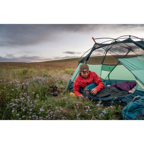Man having his coffee while sitting in a Kelty Galactic Down sleeping bag