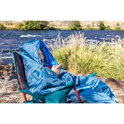 Young boy sitting in chair while wearing Kelty sleeping bag