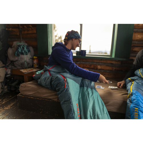Woman sitting while inside Kelty Women's Mistral 20 sleeping bag