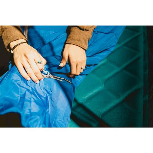 Close up of Kelty Rambler 50 Sleeping Bag, showing woman unzipping the Comfort-Tuck zipper