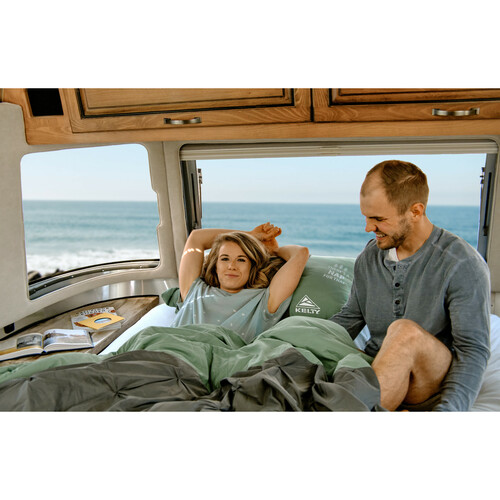 Couple camping near the ocean in Kelty Kush 30 Sleeping Bags