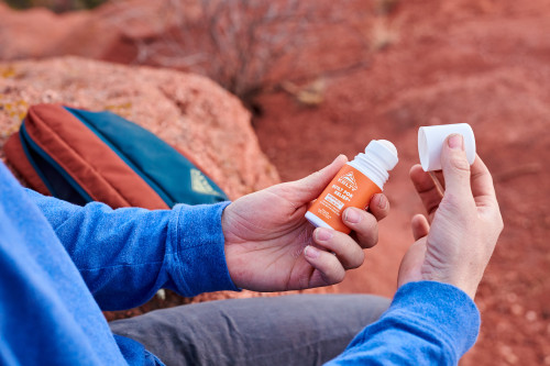 Opening the cap off the Kelty CBD Pain Relief Roll-on