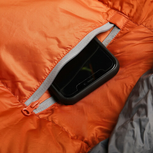 Close up of Kelty Cosmic 40 Sleeping Bag, showing phone partially extending out of small storage pocket