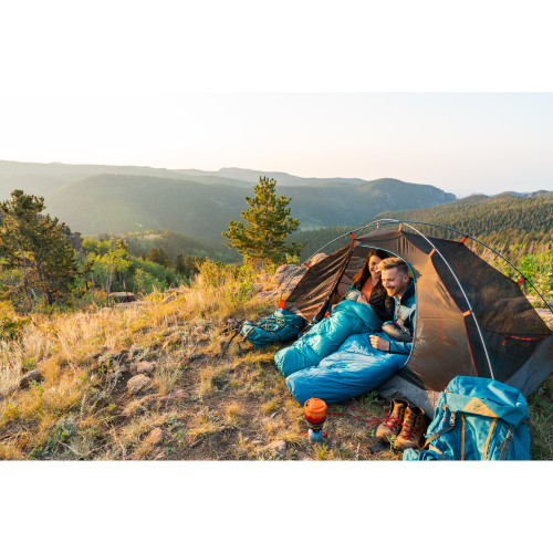 Campers in their tent with Kelty Cosmic 20 sleeping bags, exterior shot