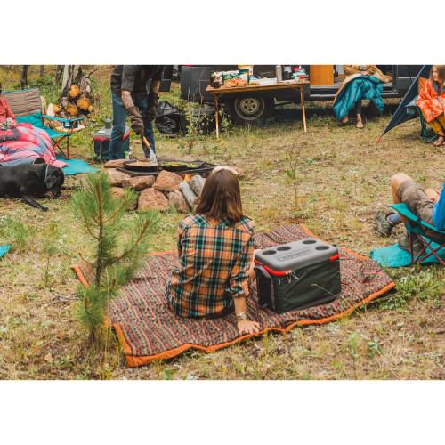 Woman at campsite sitting on Kelty Cordavan Blanket