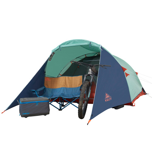 Kelty Rumpus 4 tent, front view, with fly attached, door opened, and chair placed in front of tent