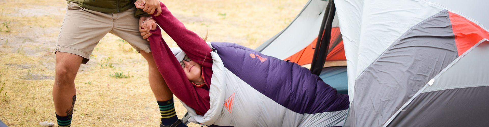 Man playfully pulling a woman out of her tent