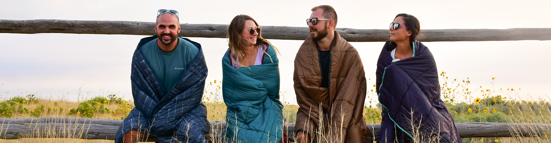 Group of four friends with Kelty camping blankets wrapped around themselves