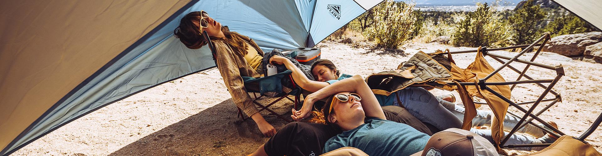 Woman sleeping under a Kelty sun shelter