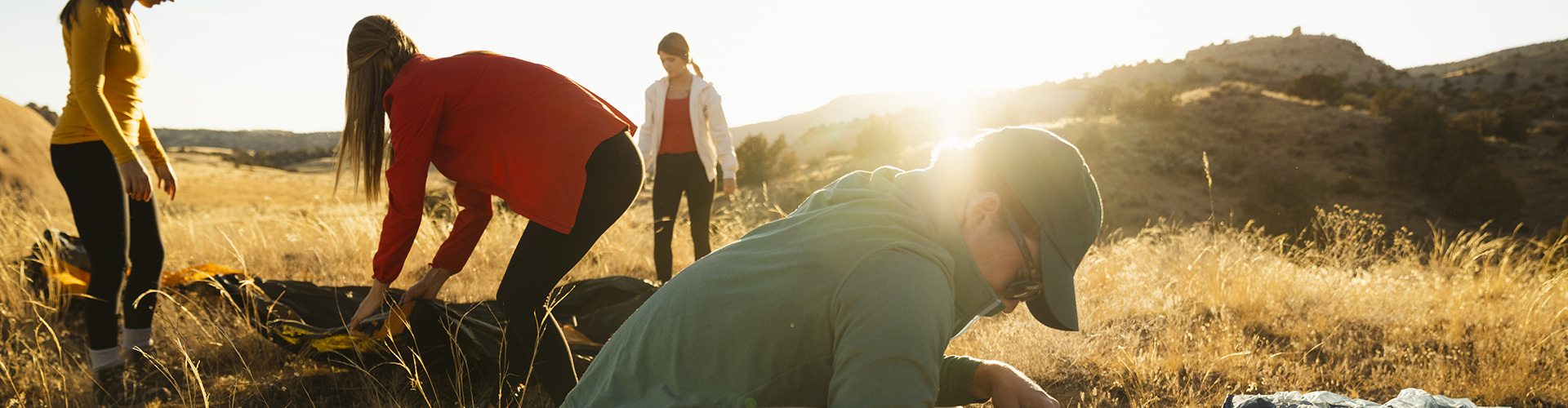 Women setting up their Kelty tent and accessories