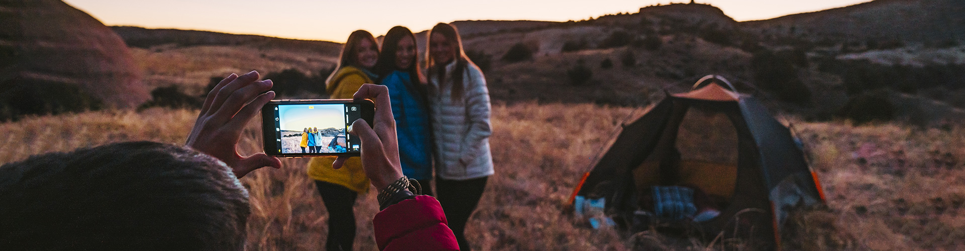 Campers taking a picture at sunset