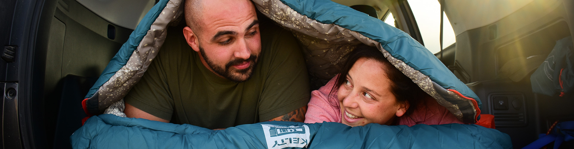 Man and woman under a Kelty sleeping bag