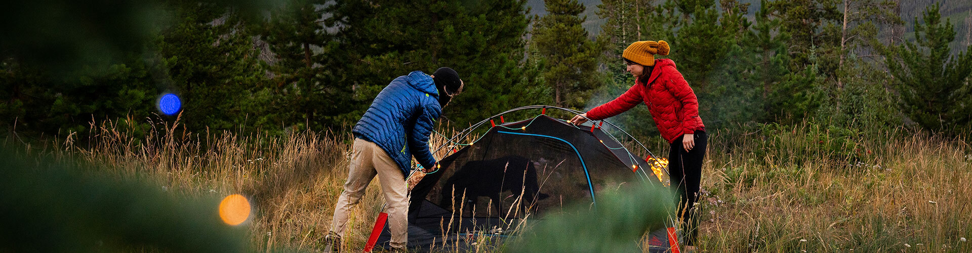 Couple in the woods putting holiday lights on their Kelty tent