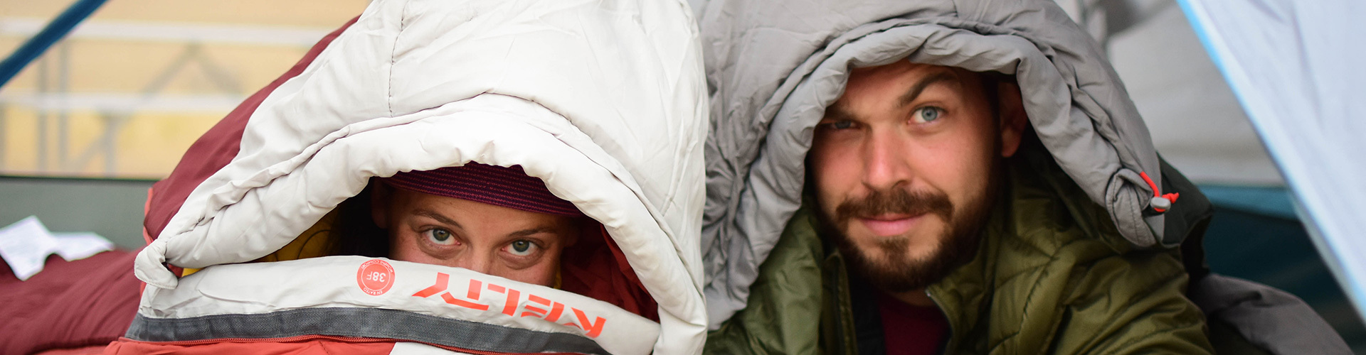 Man and woman peeking out of Kelty sleeping bags