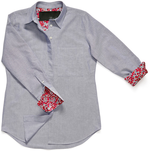 """The Modified Boyfriend Shirt is fashioned with a 100% cotton slate blue Oxford. Its sleeves and cuffs are lined with Liberty of London's cotton Tana fabric, in their classic floral pattern """"Wiltshire Bud"""", a pink, red and blue berry and leaf design."""