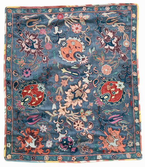 Uzbekistan mirror cover silk embroidered a medium indigo blue colored satin-finish silk cloth provides the backdrop for a medley of pleasing colors including dark puce, chalky pink, brick red, faded papaya, butter yellow, fawn, lavender-magenta, robins egg blue, indigo greens and dark blue indigo.