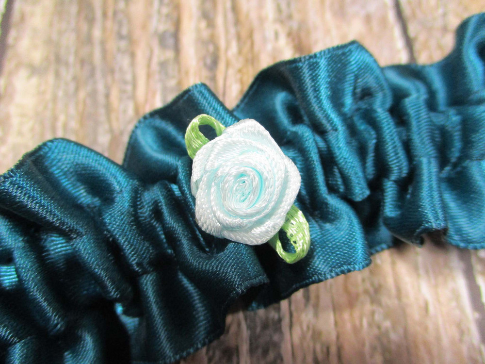 A Traditional Something Blue with a Tiny Light Blue Rose Tucked Inside the Personalized Wedding Garter