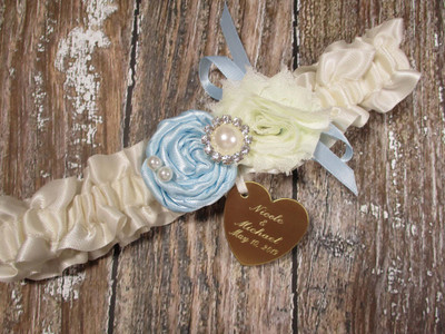 Ivory Wedding Garter in Satin Shown with a Light Blue Rose