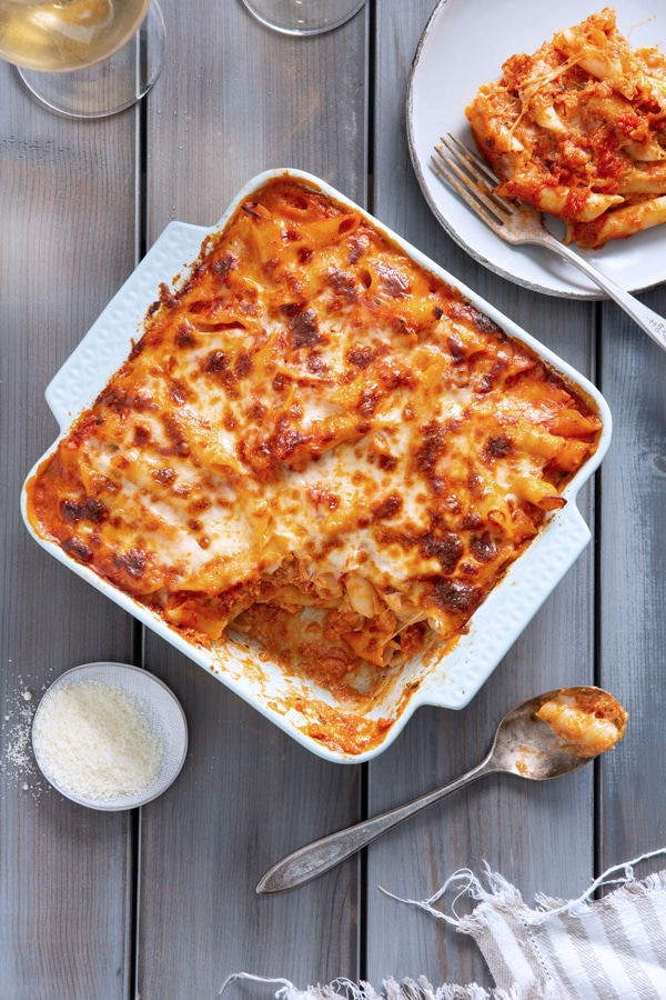 The baked pasta dish is being served out of the baking dish onto a plate.
