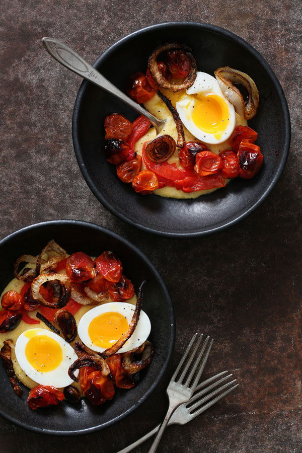 Two bowls of the cheese polenta being topped with tomatoes, onions, and eggs.