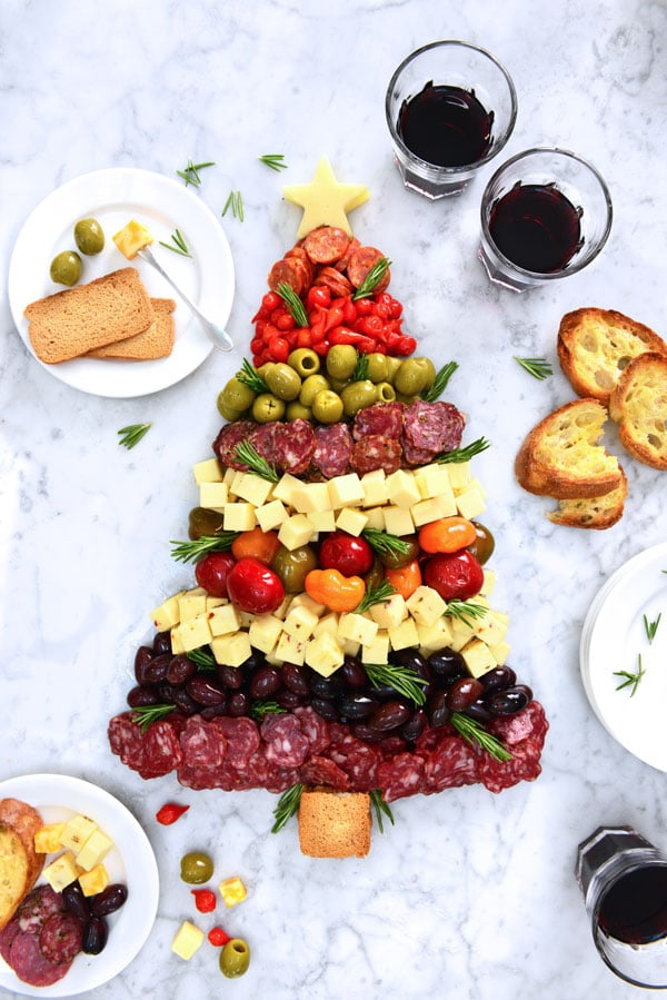 Antipastos, olives, meats, and cheeses arranged in the shape of a pine tree and served on a  counter.