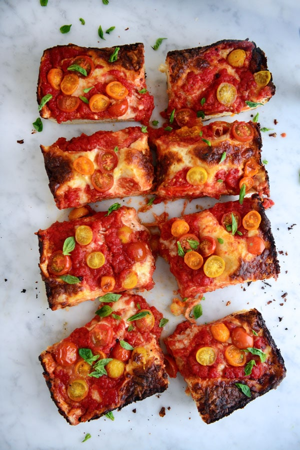 A thick Detroit styled pizza cut into pieces. The slices are topped with cherry tomatoes and sauce.