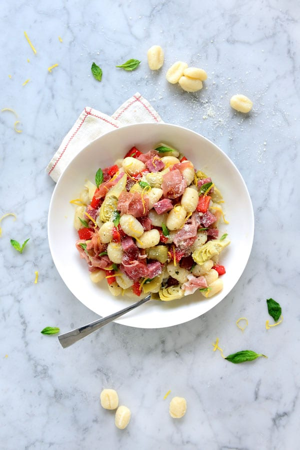 A bowl of gnocchi, salami, prosciutto, peppers, artichokes and cheese.
