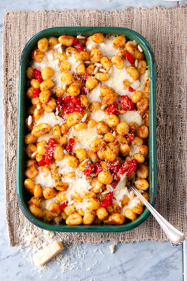 A square baking dish contains gnocchi, pepper, and cheese.
