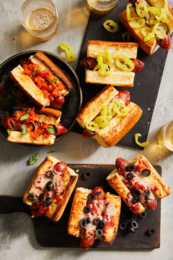 Small hot dog buns with pepperonis and topped with either bruschetta, pepper rings, or olives.