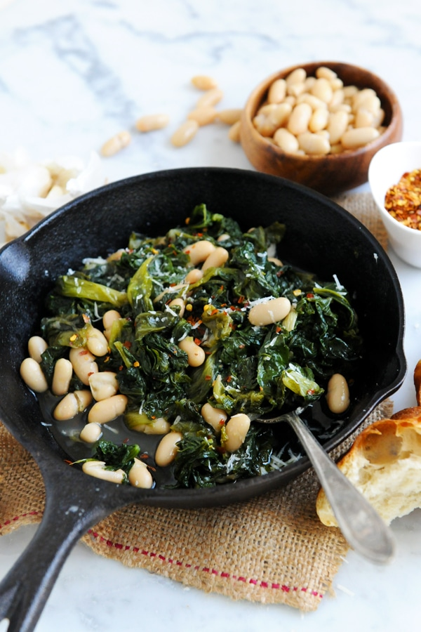 The bean and greens is being served out of a skillet.
