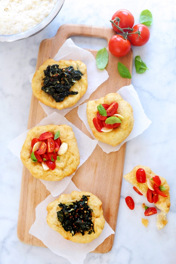 There are two of each type of fried pizza on a wooden cutting board. One fritta  type is topped with tomoates, and garlic. Another fritta is topped with kale.
