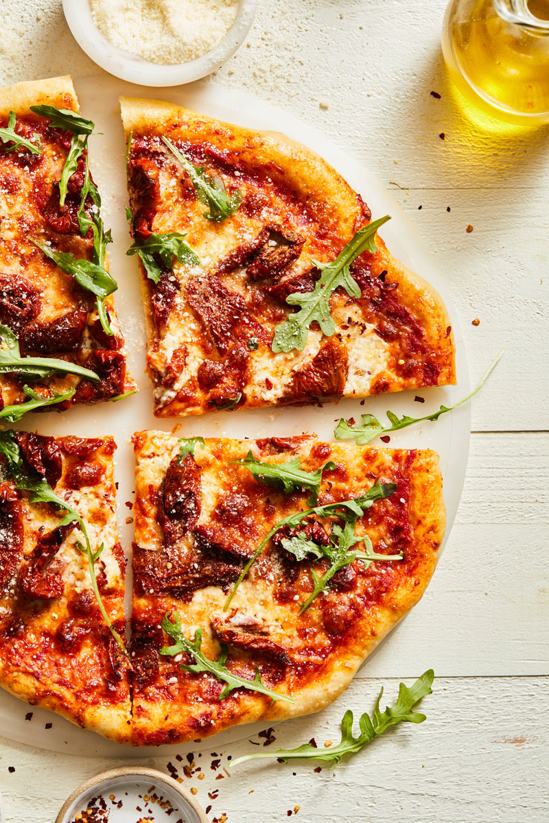 A square pizza cut into pieces topped with arugula.
