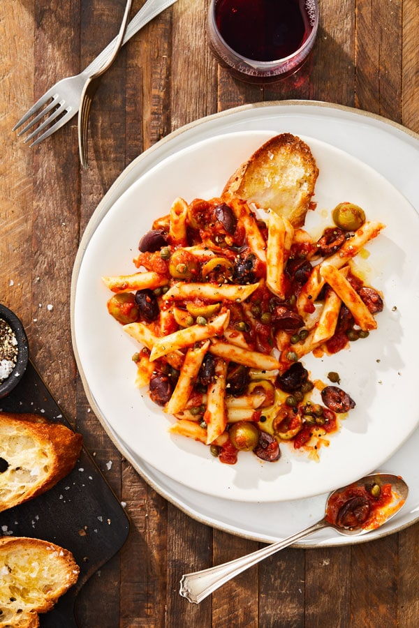 A plate of this pasta being served with toasted Italian bread and wine.