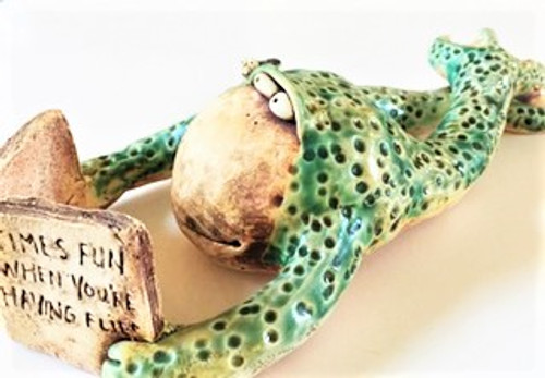 "Hand sculpted stoneware frog holds a book entitled ""Times Fun When You're Having Flies"" textured with a round ended dowel, stained, glazed and high fires.  Hand Painted with green, black and off white glazes.  Fly incorporated in this sculpture next to eyes. Width:  5"" Height:  3"" Depth:  12"""